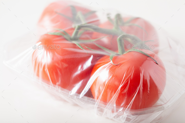 single use plastic packaging issue. tomatoes vegetables in plastic bag - Stock Photo - Images