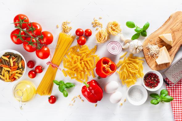 ingredients for italian cousine flat lay, pasta spaghetti penne fusilli tomato oil vegetables - Stock Photo - Images