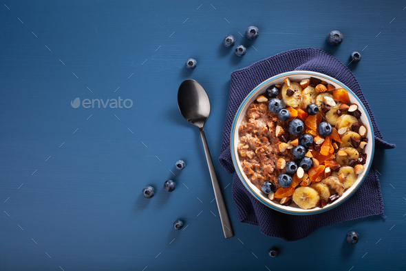 chocolate oatmeal porridge with blueberry, nuts, banana, dried apricot for healthy breakfast - Stock Photo - Images
