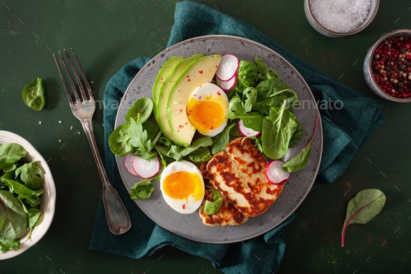 healthy keto paleo diet breakfast: boiled egg, avocado, halloumi cheese, salad leaves - Stock Photo - Images