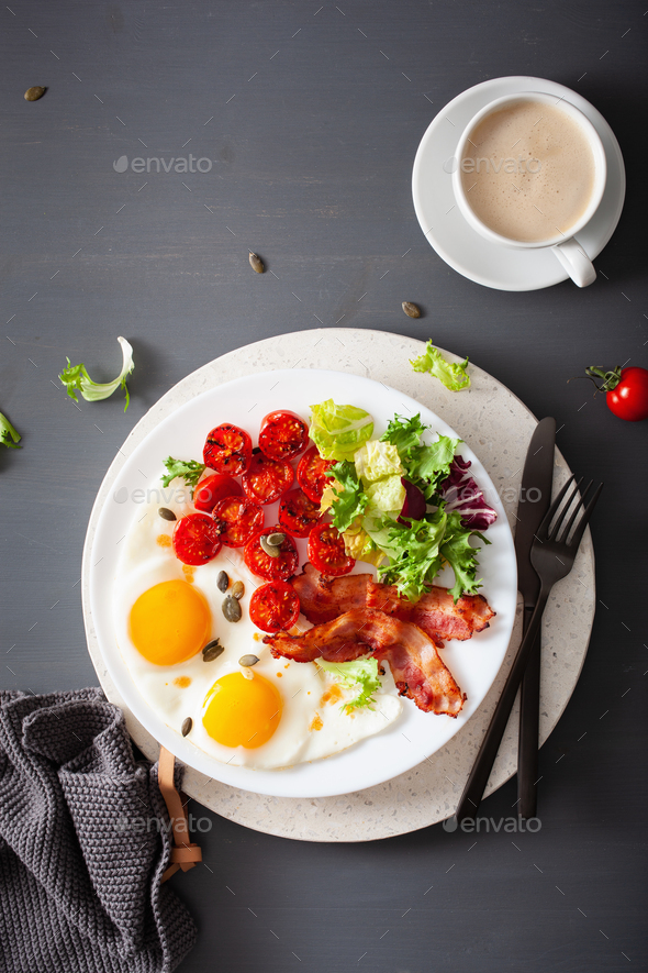 healthy keto diet breakfast: egg, tomatoes, salad leaves and bacon - Stock Photo - Images