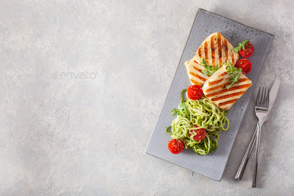 ketogenic paleo diet lunch. halloumi cheese, spiralized zucchini with arugula pesto and tomatoes - Stock Photo - Images