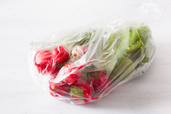 single use plastic packaging issue. radish vegetable in plastic bag - Stock Photo - Images