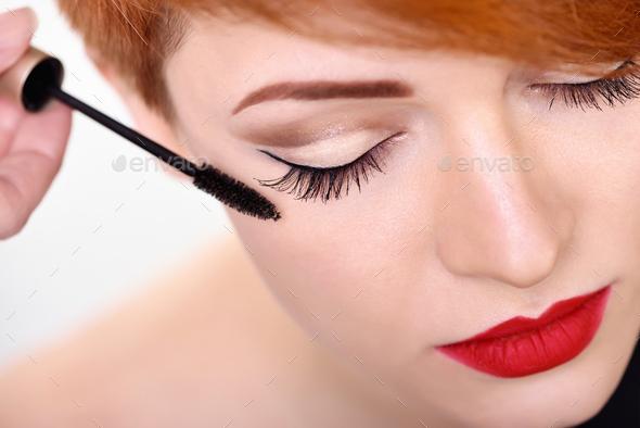 Makeup artist applies mascara brush. Beautiful young woman with short red hair. Makeup detail. - Stock Photo - Images