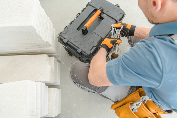 Male Building Contractor Sorts Through Toolbox To Find Needed Materials. - Stock Photo - Images