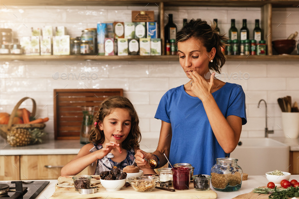 Little girl cooking with her mother in the kitchen. - Stock Photo - Images