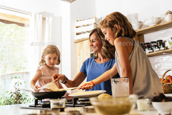 Little sisters cooking with her mother in the kitchen. - Stock Photo - Images