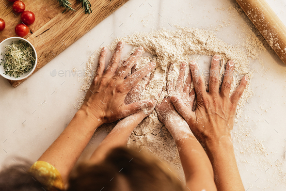 Little girl kneading flour with her mother. - Stock Photo - Images