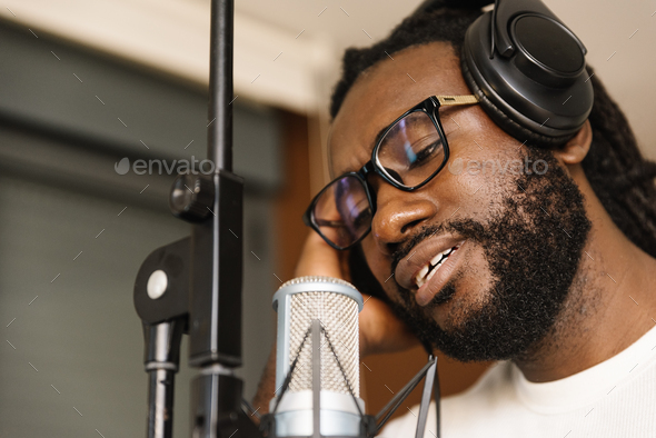 African young man singing on musical studio. - Stock Photo - Images