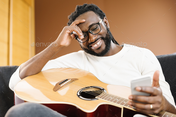 Guitarist with guitar using mobile. - Stock Photo - Images