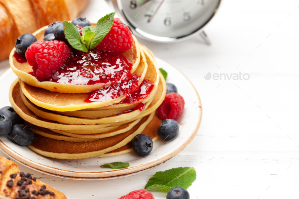 Delicious pancakes with berries and jam, croissants and coffee - Stock Photo - Images