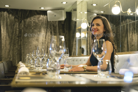 Beautiful young girl in luxury restaurant interior waiting - Stock Photo - Images