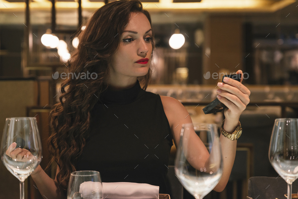 Attractive female use mirror to makeup in restaurant - Stock Photo - Images