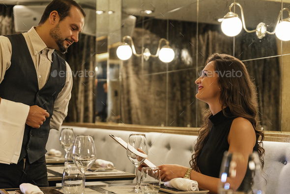 Young attractive woman making order at restaurant - Stock Photo - Images