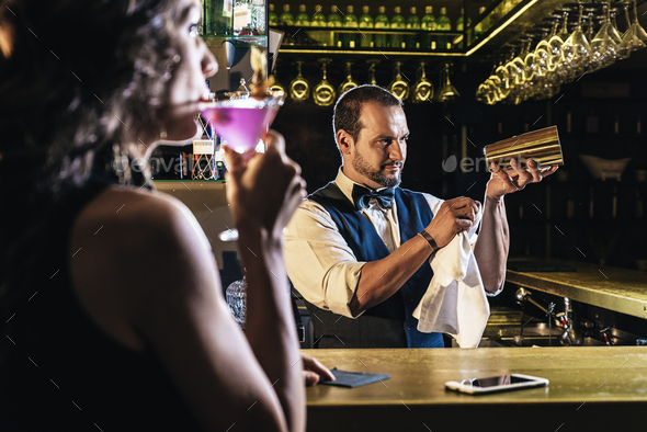 Handsome bartender serving cocktail to beautiful woman - Stock Photo - Images