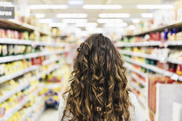 Back view of Beautiful woman buying food in supermarket. - Stock Photo - Images
