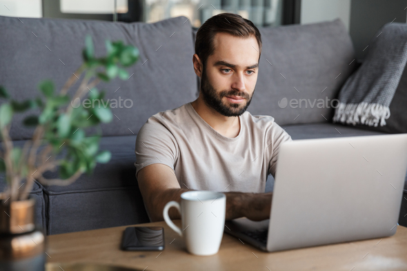 Concentrated young man using laptop computer. - Stock Photo - Images