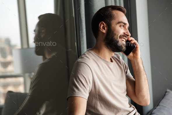 Happy cheerful young man talking by mobile phone. - Stock Photo - Images