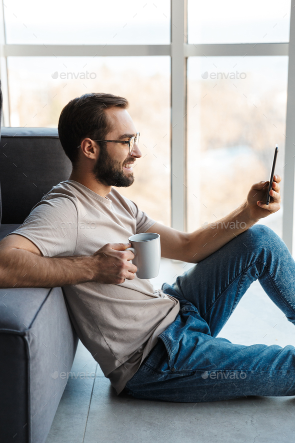 Optimistic young man indoors drinking coffee - Stock Photo - Images