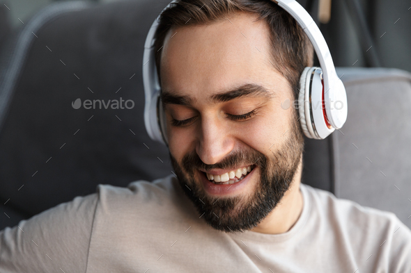 Positive young man indoors at home listening music - Stock Photo - Images