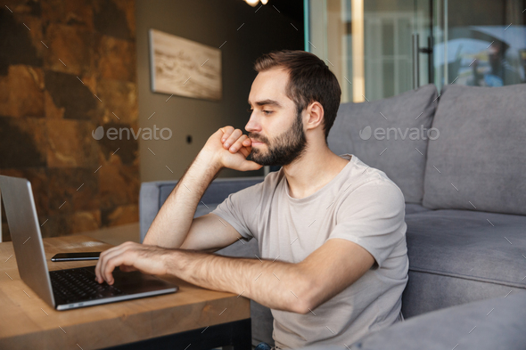 Attractive smart young man sitting on a floor in the living room - Stock Photo - Images