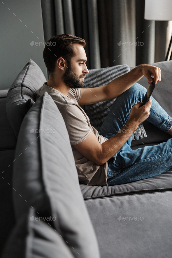 Concentrated young man indoors at home on sofa - Stock Photo - Images