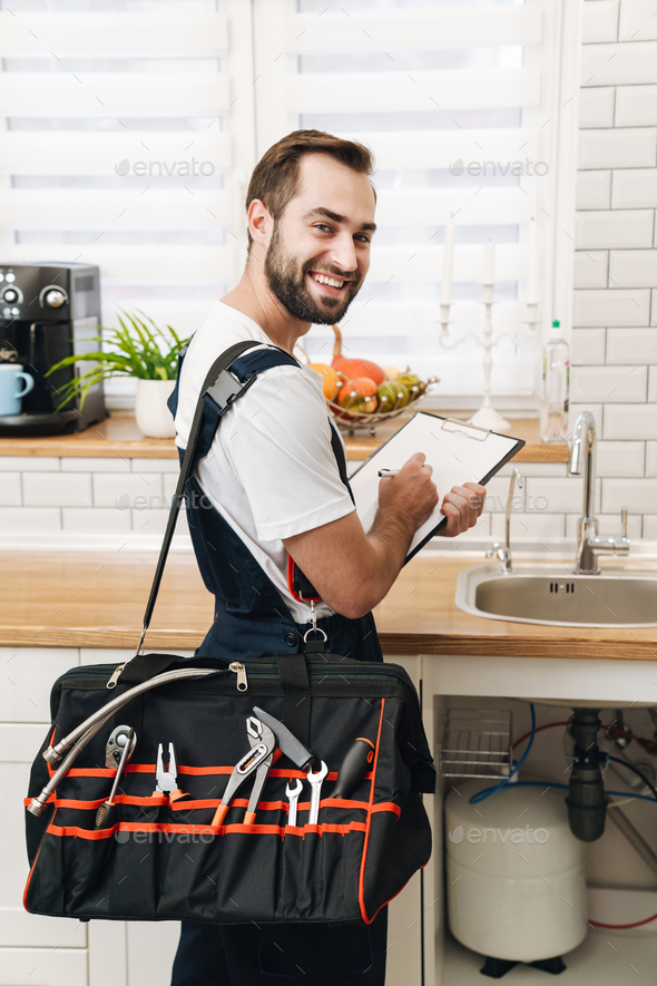 Image of plumber man with equipment and clipboard working in apartment - Stock Photo - Images