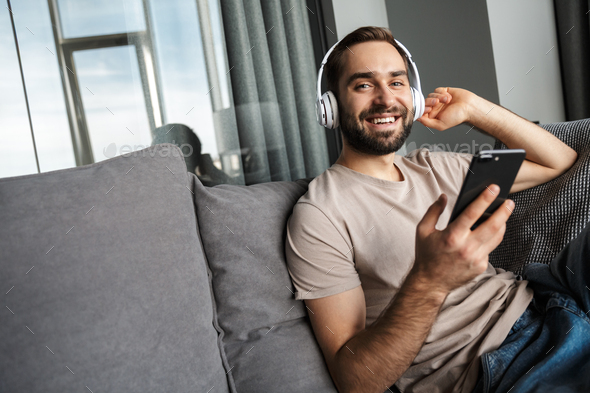 Positive man listening music with headphones - Stock Photo - Images