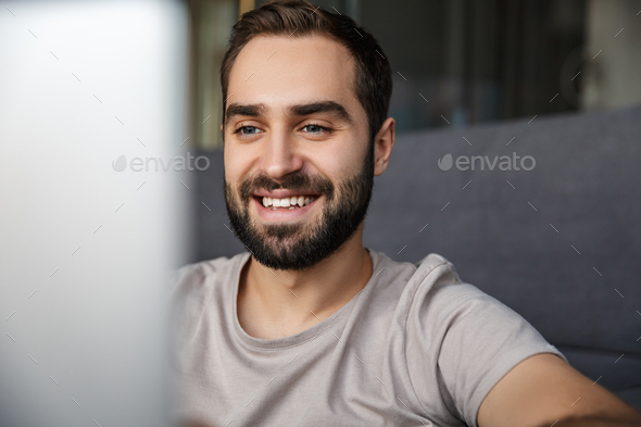 Man indoors at home on sofa using laptop computer. - Stock Photo - Images