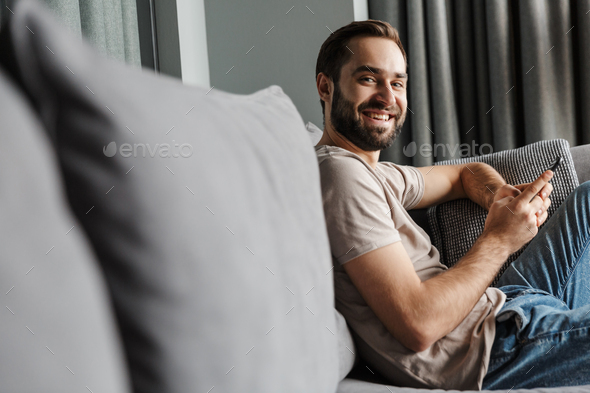 Positive young man indoors at home on sofa - Stock Photo - Images