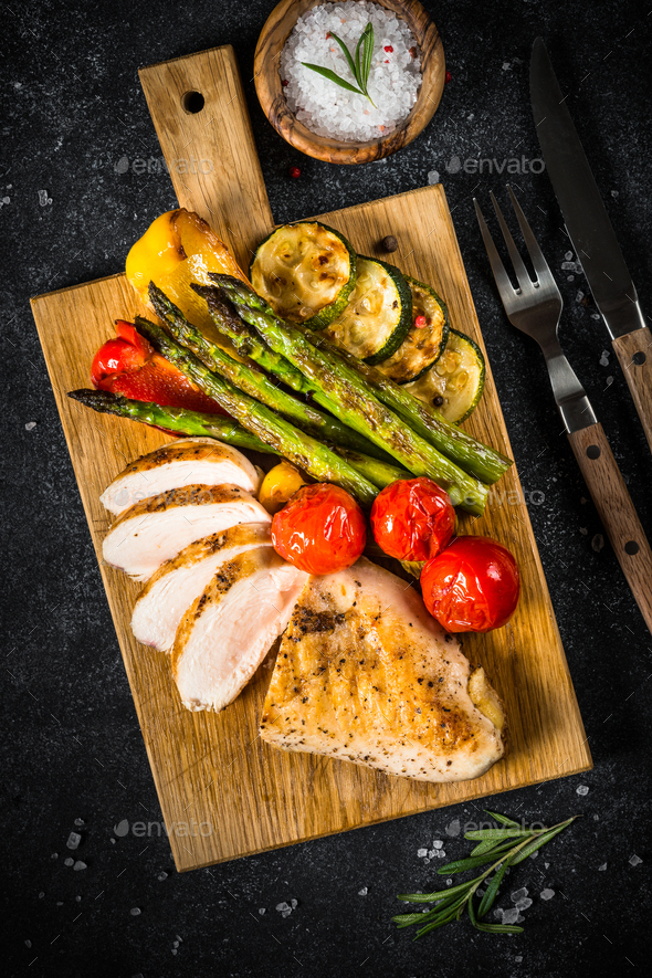 Chicken breast grilled with vegetables on black table - Stock Photo - Images