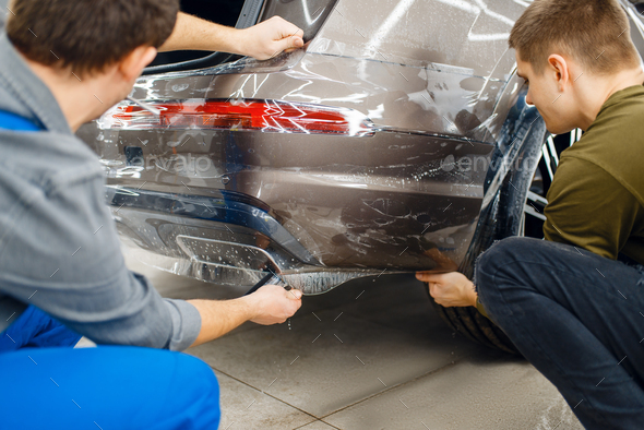 Two workers applies car protection film on bumper - Stock Photo - Images