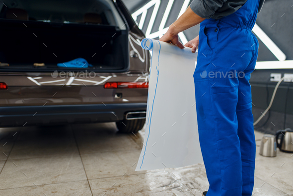 Male worker holds roll of car protection film - Stock Photo - Images