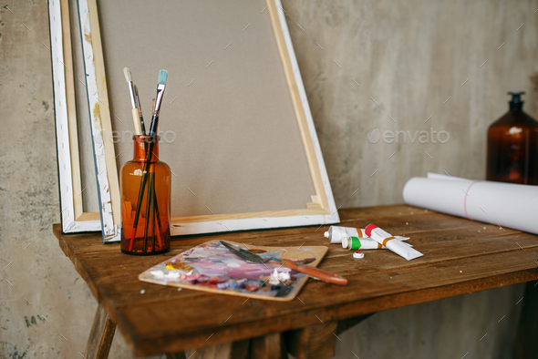 Paints on palette, brush in bottle, canvas, nobody - Stock Photo - Images