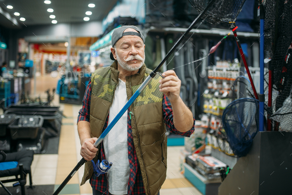 Angler puts line in the eye of rod, fishing shop - Stock Photo - Images