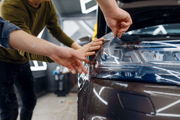 Workers applies car protection film on fender - Stock Photo - Images