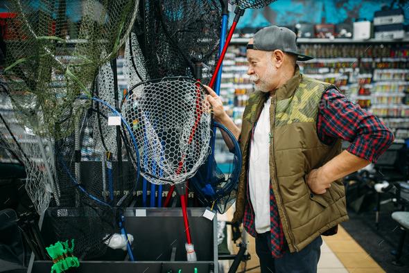 Happy fisherman choosing net in fishing shop - Stock Photo - Images
