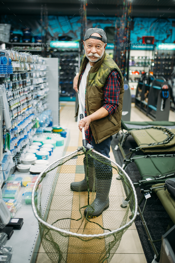 Happy angler holds net in fishing shop - Stock Photo - Images