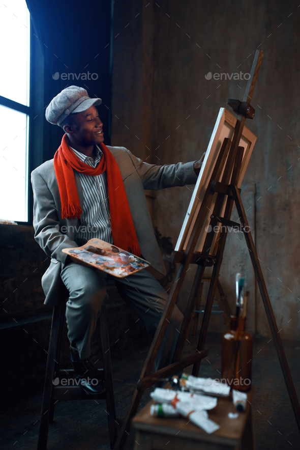Fashionable painter with palette poses at easel - Stock Photo - Images