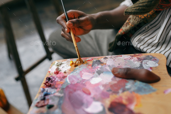 Painter holds brush and colorful paints on palette - Stock Photo - Images