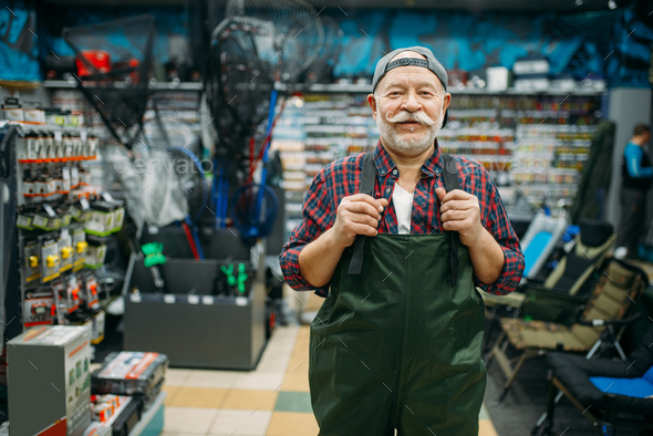 Fisherman tries on rubber jumpsuit in fishing shop - Stock Photo - Images