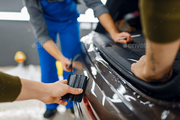 Two workers smoothes car protection film on bumper - Stock Photo - Images