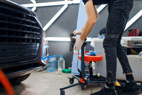 Male worker dries car protection film, auto tuning - Stock Photo - Images