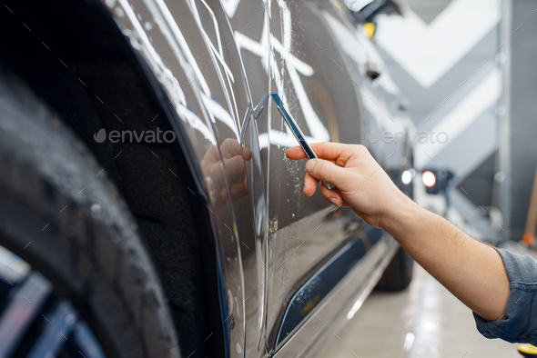 Specialist cuts protection film on car surface - Stock Photo - Images