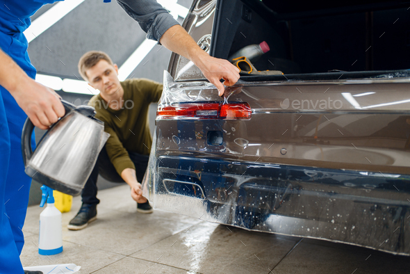 Specialists applies car protection film on bumper - Stock Photo - Images
