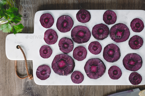 Overhead view on slices of raw purple carrot on a white marble board over kitchen table. - Stock Photo - Images