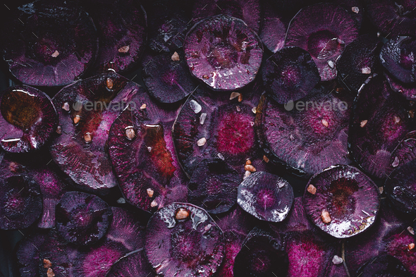 Slices of purple carrot with pink salt and olive oil for roasting. Macro photography, top view. - Stock Photo - Images