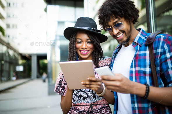 Young modern stylish couple using tablet in urban city - Stock Photo - Images