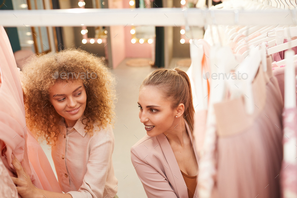 Two Young Women Choosing Dresses in Boutique - Stock Photo - Images