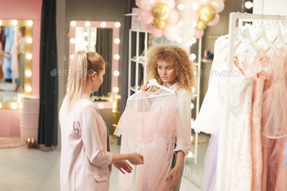 Shop Assistant Helping Client in Clothing Boutique - Stock Photo - Images